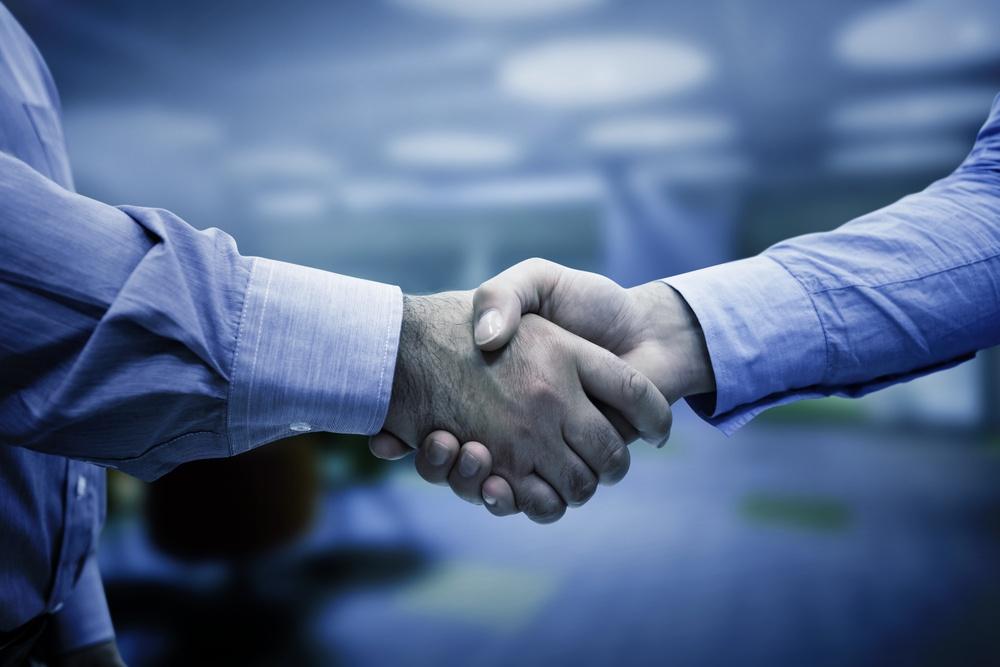 Men shaking hands against college